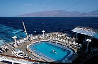 Chain of islands. North Atlantic. Swimming pool on cruise ship deck. View of mountains,island.