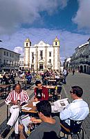 Four men seated reading newspapers at Cafe table in square outside the Praca do Geraldo.