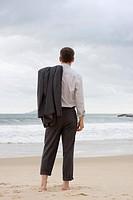Geschäftsmann steht barfuß am Strand