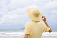 Frau mit Hut schaut aufs Meer