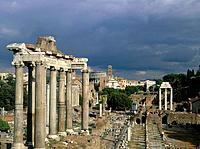 The Roman Forum site,the archaeological layout and stone carved buildings and architecture. The temple of Saturn and triumphal archway.