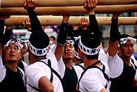 The Okunchi Shinto religious festival parade. Men in traditional black and white costumes holding and supporting the poles underneath a float