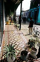 Street. Walkway. Colonial style terrace of houses. doors. Tiled floor. Pot plants. Man with bicycle.
