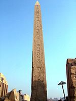 Temple of Karnak. Tall stone column,the obelisk of Thot_Mosis I reaching to the sky. Carved symbols. Hieroglyphics.