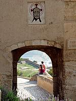 Castillo Santa Barbara castle. Thick stone walls.,Hilltop fortification. Path up slopes to small arched entrance. Couple sitting on wall by archway. V...