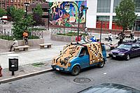 Harlem black neighbourhood. Street. Small park area. Square. People sitting on benches. Cars parked. Van covered with large carpets. Rugs for sale. Mu...