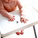 Baby girl sitting in high chair reaching for vitamins
