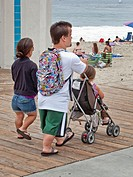 Midget parents push their normal size daughter in a stroller at Laguna Beach, CA