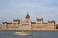 Sightseeing ferry going past Orszaghaz the Parliament House along Danube river Budapest Hungary Europe