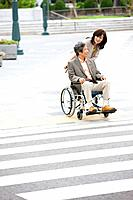 Mature woman talking to senior man on wheelchair