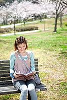 Young woman sitting on bench reading a book