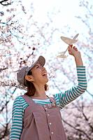Young woman with paper airplane