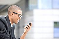 Young African businessman looking at phone