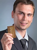 Smiling businessman holding a gold credit card in his hands