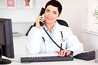 Smiling female doctor making a phone call in her office