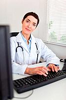 Portrait of a smiling female doctor typing with her computer in her office