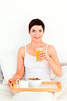 Woman drinking orange juice in her bedroom