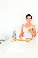 Portrait of a woman holding a glass of juice in her bedroom