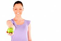 Pretty woman holding an apple while standing against a white background