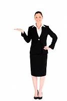 Charming woman in suit showing a copy space while standing against a white background