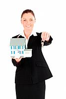 Pretty woman in suit holding keys and a miniature house while standing against a white background
