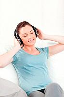 Lovely woman relaxing with headphones while sitting on a sofa in the living room