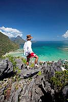 man enjoys view from limestone spires over coastal village, el nido, palawan, philippines