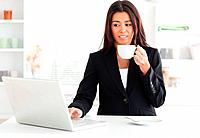 Gorgeous woman in suit enjoying a cup of coffee while relaxing with her laptop in the kitchen
