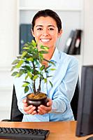 Gorgeous woman holding a plant while looking at the camera at the office