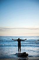 a person with arms outstretched looking at the sky while standing on a piece of driftwood at the ocean´s edge, la push washington united states of ame...
