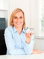 Gorgeous blonde businesswoman showing miniature house looking into the camera in her office