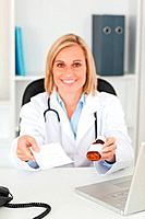 Smiling blonde doctor holding prescription and medicine looks into camera in her office