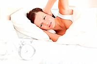 Gorgeous red_haired woman lying in bed not wanting to hear the alarm clock in her bedroom