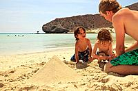 three boys play in the sand at the water´s edge at los islotes national marine park espiritu santo island, la paz baja california mexico