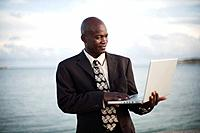a businessman using a laptop computer by the water´s edge, south caicos turks and caicos islands