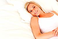 Blonde woman lying on her bed looking at the camera