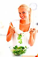 Portrait of a woman mixing a salad in her kitchen