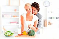 Young couple slicing pepper in their kitchen
