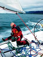 Man adjusting rigging on sailboat