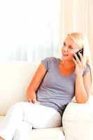 Portrait of a blonde woman on the phone in her living room