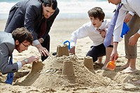 Businessmen building sand castle