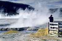 Tourist at boardwalk over look at Cliff Geyser, Black Sand Basin, Yellowstone National Park, WYOMING