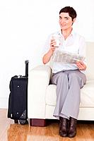 Brunette woman with a suitcase, a newspaper and a cup in a waiting room