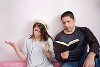 Father reading to his teen daughter who is listening to music on her iPod