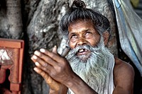 A Holy Man Sits Looking Upwards With Hands Raised, Haridwar India