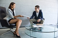 Businesswoman handing documents to client