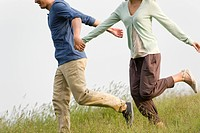 Couple holding hands running on meadow, cropped