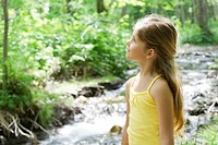 Girl standing beside stream, looking up in awe