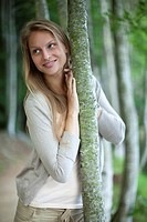 Woman leaning against tree trunk, portrait