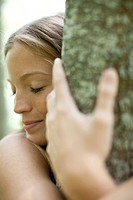 Young woman hugging tree with eyes closed, cropped